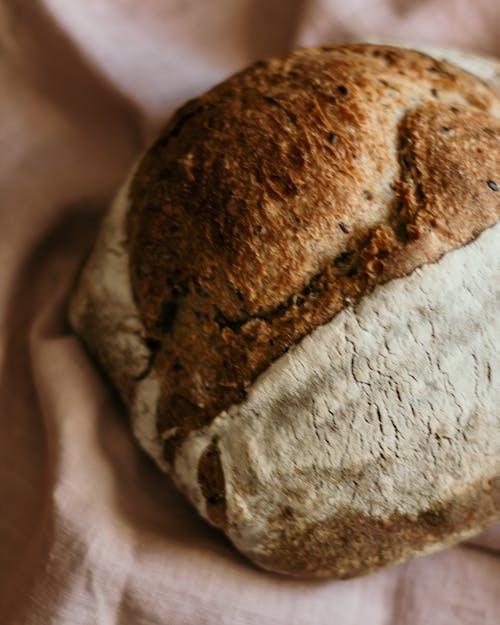 Loaf of sourdough bread on crumpled cloth