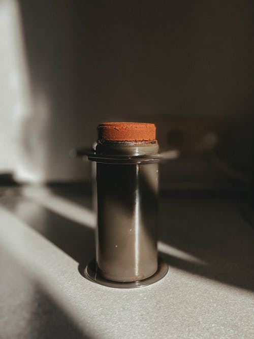 Ground coffee beans in cylindrical aeropress placed on table in kitchen at sunlight