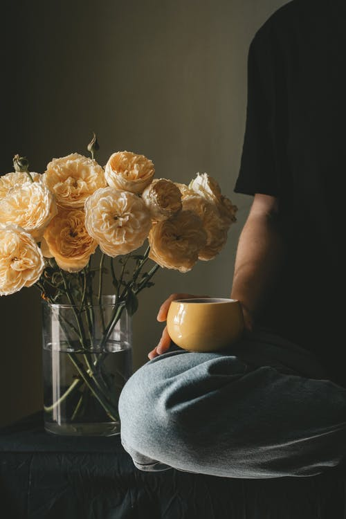 Unrecognizable person with cup of hot coffee sitting with crossed legs near vase with blooming roses near wall in room