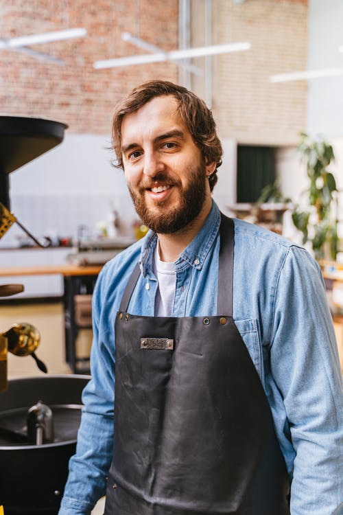 Man in Blue Button Up Shirt and Black Apron
