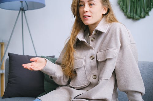 Crop female with long hair in elegant clothes sitting on comfortable sofa while talking in light room during psychotherapy session