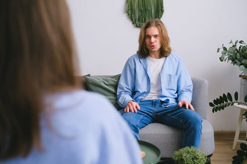 Concerned male client siting on sofa while having conversation about problems with faceless psychologist during psychotherapy appointment in light office