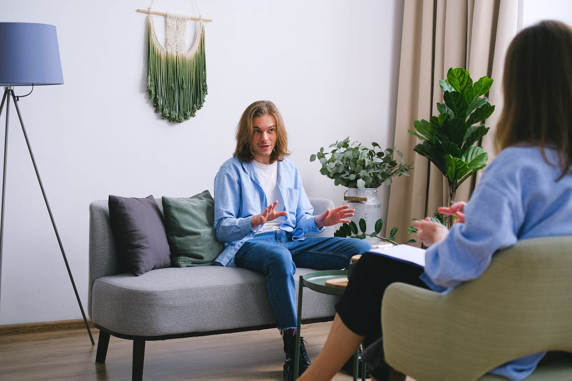 Worried male patient sitting on couch while having conversation about problems with unrecognizable professional psychologist during psychotherapy appointment in office