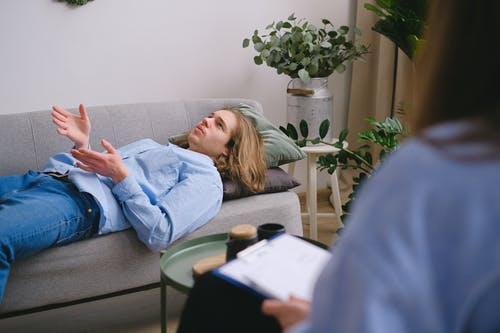 Concerned male client lying on sofa and speaking about mental problems with unrecognizable psychologist with clipboard during psychotherapy appointment in office