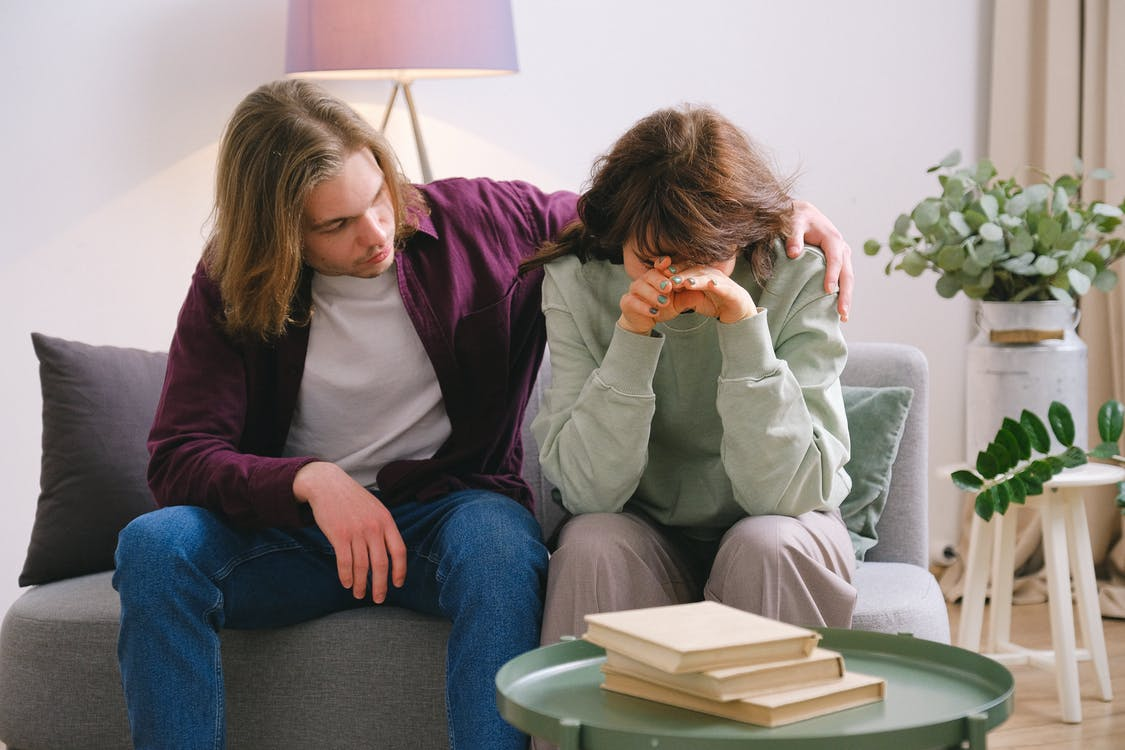 Young male in jeans comforting depressed upset female crying on gray sofa near table with books