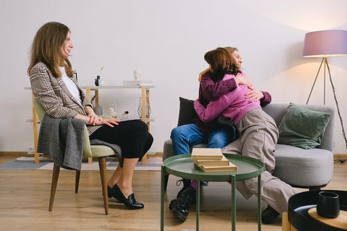 Side view of positive female therapist looking at loving couple cuddling on sofa near table with books