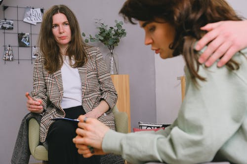 Man touching shoulder of woman talking with psychologist