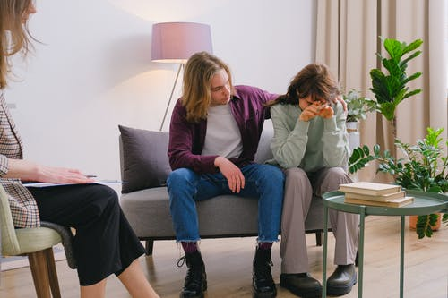 Young male embracing frustrated girlfriend during session with psychologist in light room in daytime