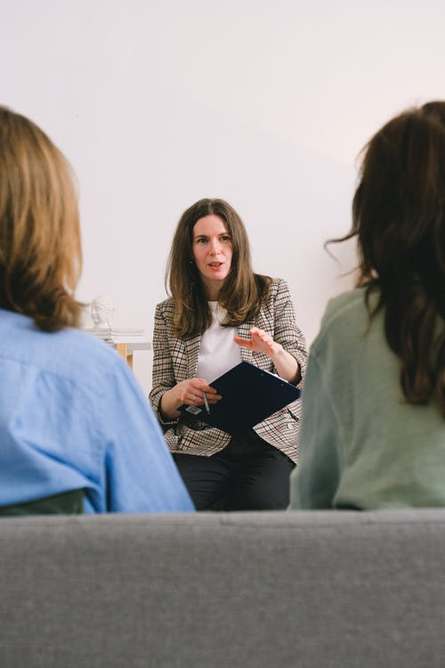 Pensive woman entrepreneur with brown hair in casual clothes sitting with clipboard and talking with unrecognizable clients in light room