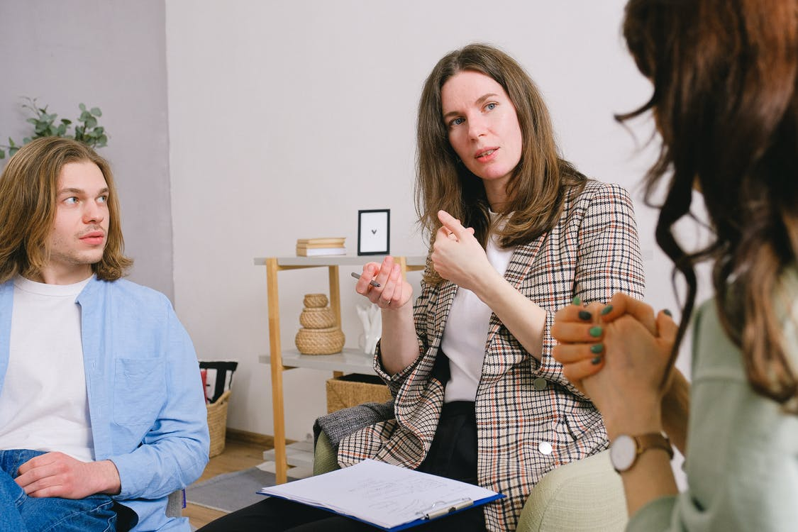 Thoughtful woman psychologist in stylish clothes siting with clipboard and talking with couple in light room