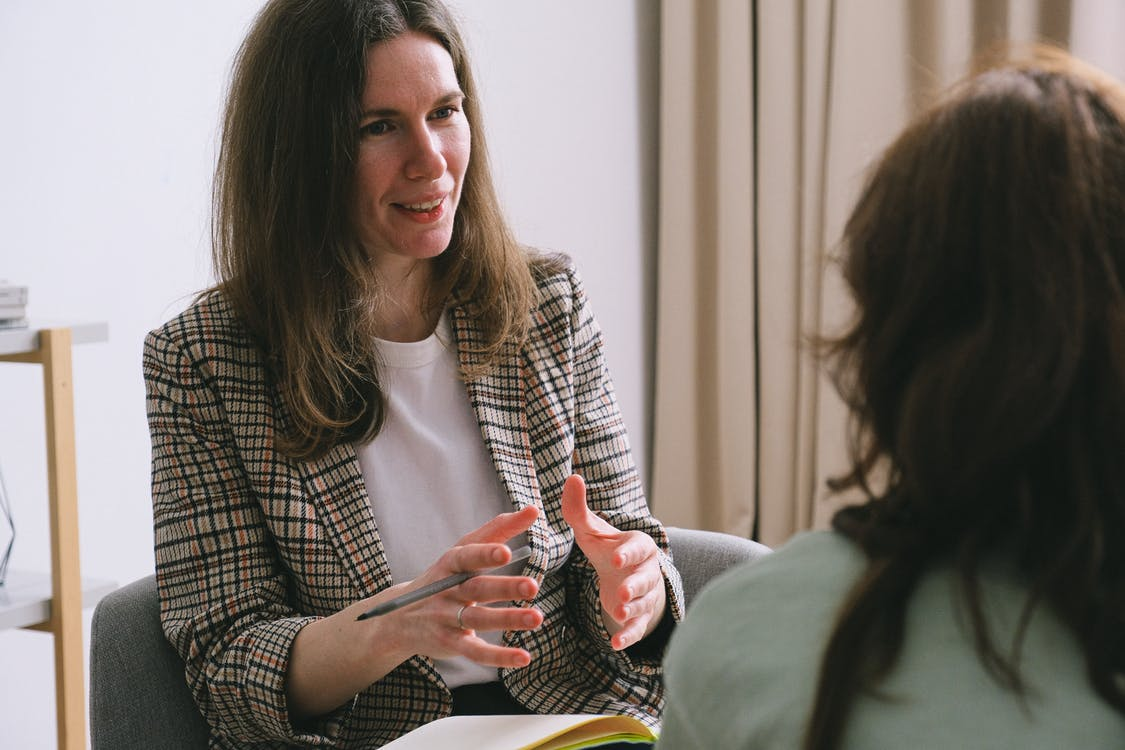 Pensive woman psychologist with brown hair in stylish clothes sitting and talking with unrecognizable female in light room