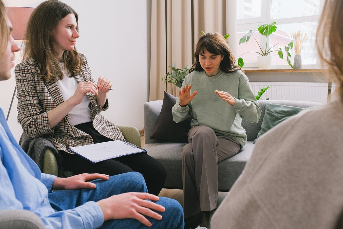 Women in casual clothes sitting on sofa and speaking during group psychotherapy session in cozy office