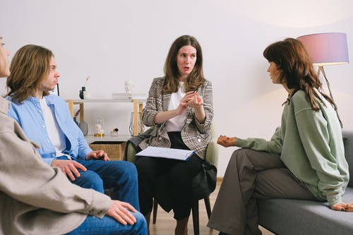 Female therapist during group session talking to female patients gathering in light cozy office