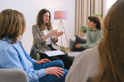 Young female therapist sitting on chair and discussing problem with patients during psychotherapy session in group