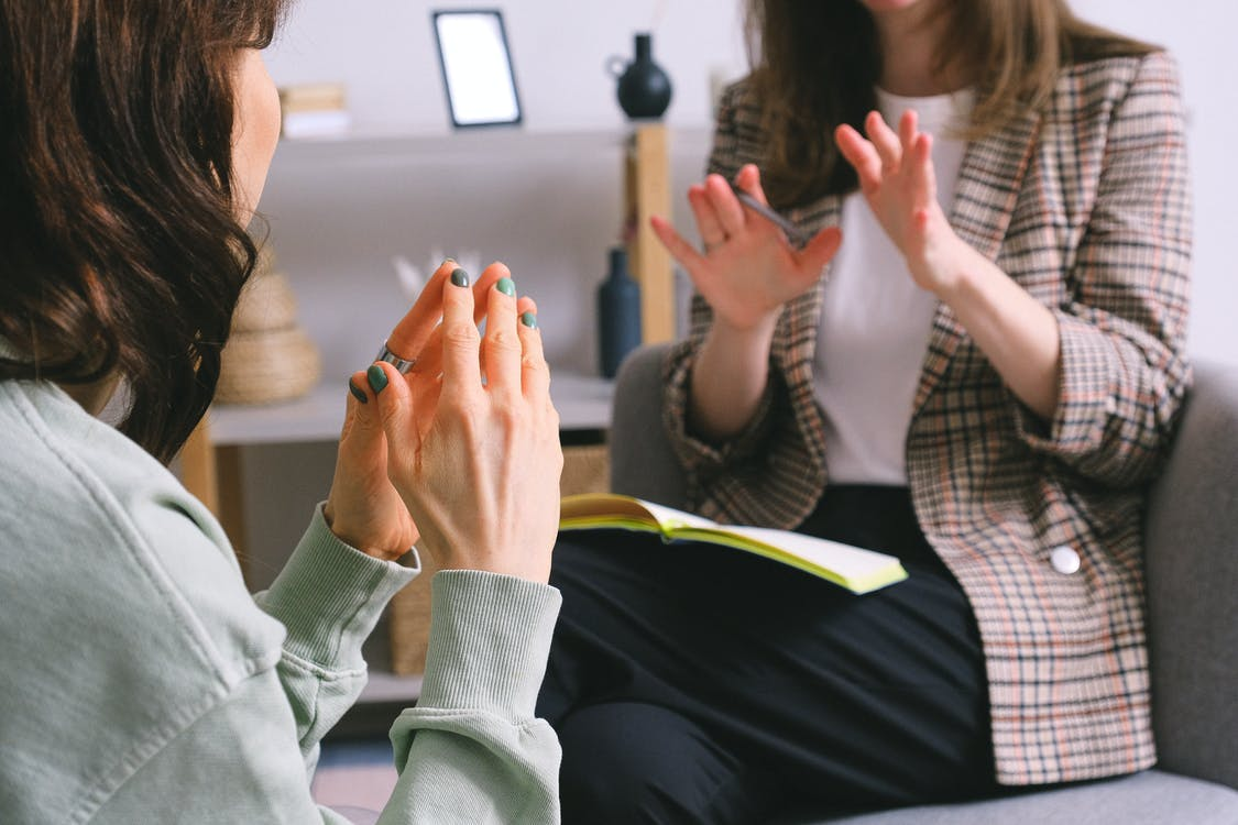 Crop unrecognizable female psychologist and patient discussing mental problems during session