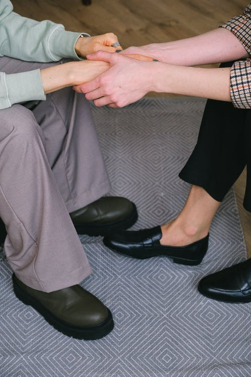 From above of crop unrecognizable psychotherapist holding hands of woman while interacting during counseling on carpet