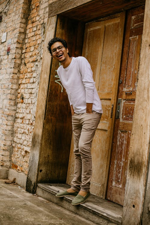 Man in White Long Sleeve Shirt and Brown Pants Standing Beside Brown Wooden Door