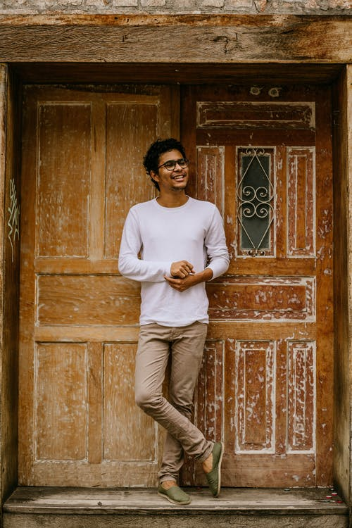 Man in White Crew Neck Long Sleeve Shirt and Brown Pants Standing Beside Brown Wooden Door