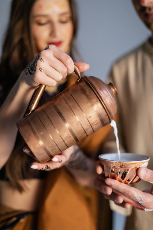 Unrecognizable ethnic couple pouring milk into bowl