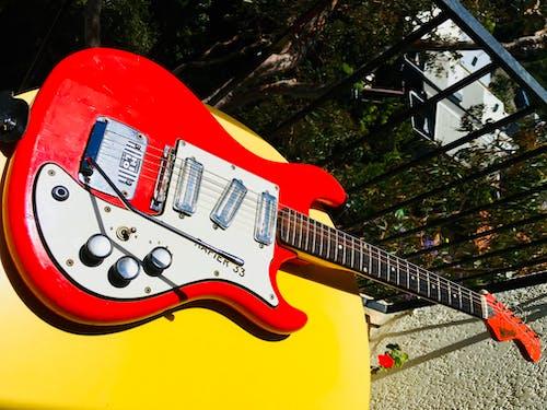 Immagine gratuita di chitarra elettrica, chitarra rossa, tavolo giallo