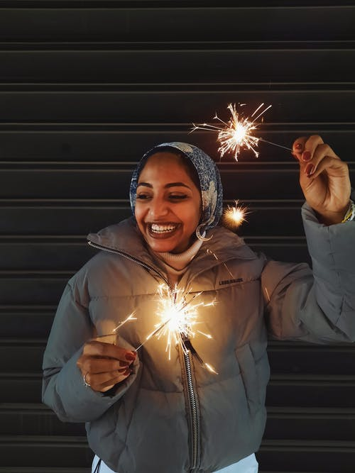 Joyful Indian female in outerwear and headscarf with glowing Bengal lights laughing happily against metal gates