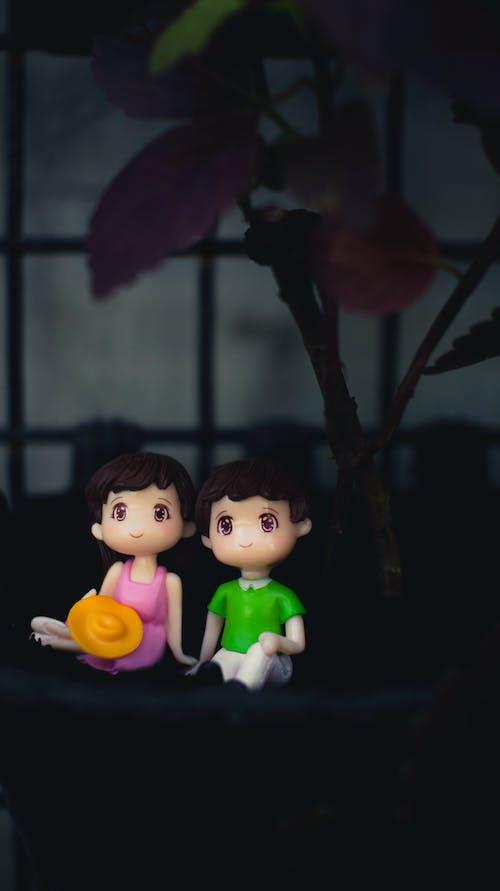 Cute couple figurines near plant
