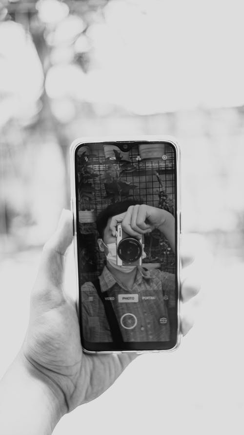 Man with photo camera taking selfie on smartphone