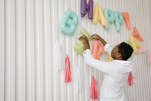 Photo of a Man in a White Dress Shirt Setting Up Birthday Balloons