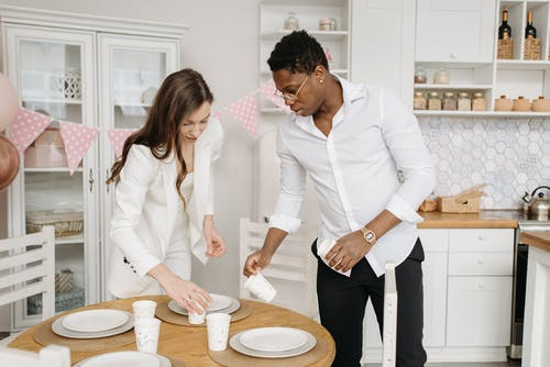 Man and Woman Setting the Table
