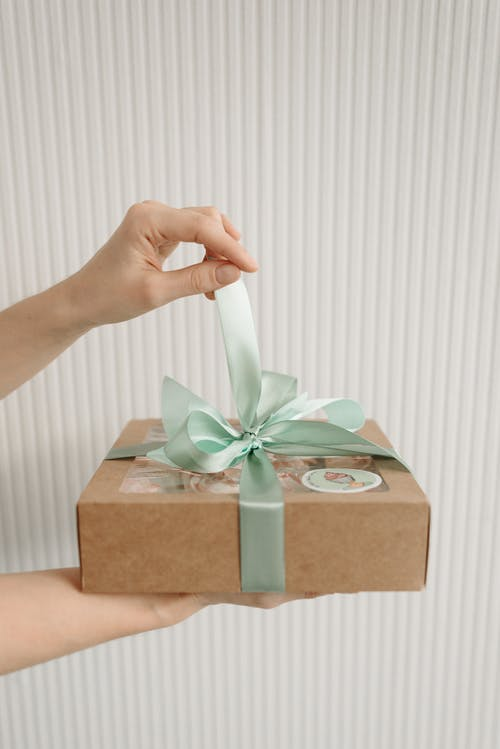 Close-Up Shot of a Person Opening a Box of Cupcakes