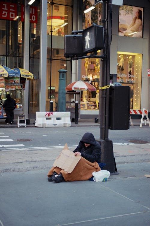 Man in Black Jacket Sitting on Sidewalk