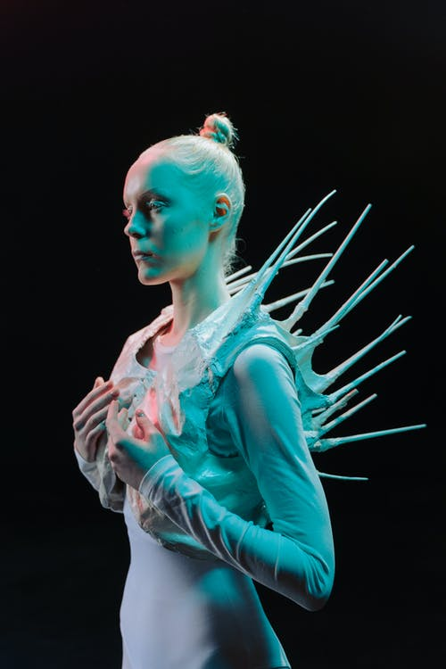 Woman in Futuristic White Costume on a Black Background