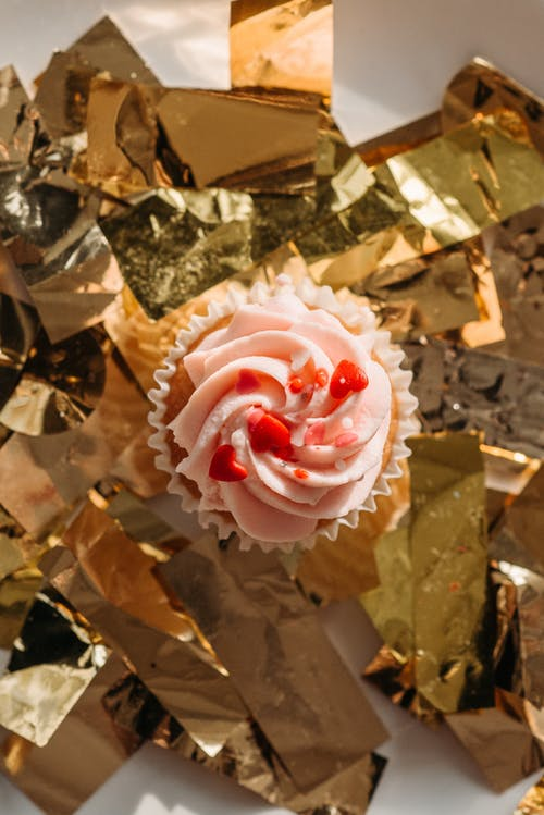 Top View of a Cupcake with Whipped Cream on Golden Confetti
