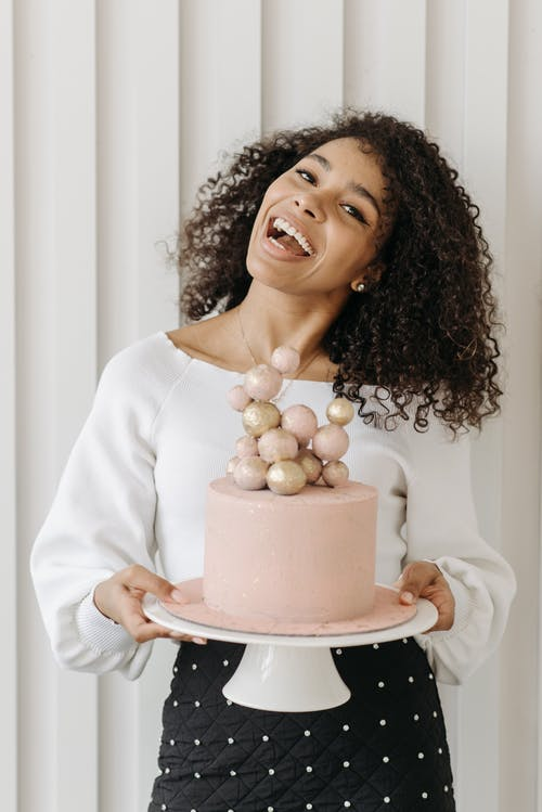 Woman with Curly Hair Holding a Pink Cake