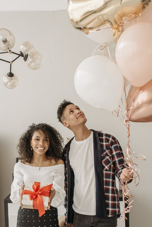Woman in White Blouse Standing Beside a Man Wearing a Checkered Long Sleeve while Holding Balloons