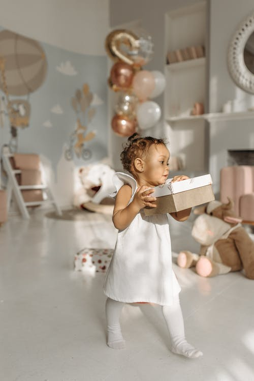 Child Carrying Her Birthday Gift