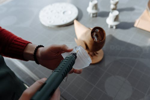 Person Putting Glue on the Dome Plastic Piece from a Glue Gun
