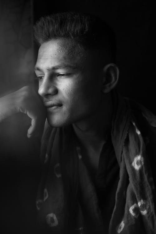 Peaceful Indian man in dark studio