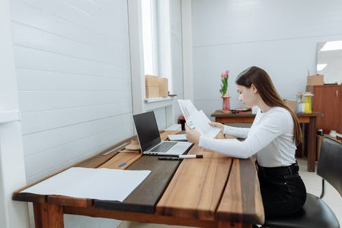 Woman in White Long Sleeve Shirt Sitting at the Table Using Laptop Computer
