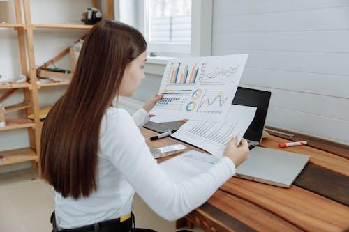 Woman Analyzing the Design Business Progress Reports
