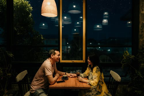 Man and Woman Sitting on Brown Wooden Table