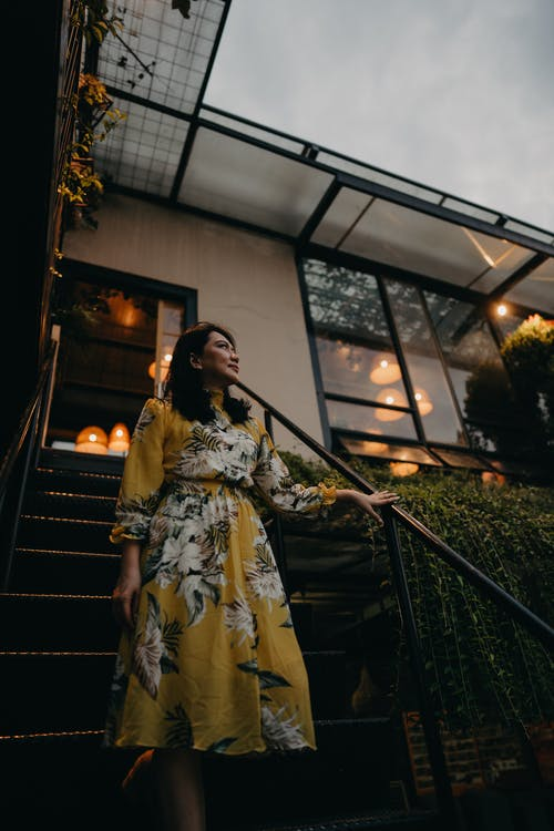 Woman in Yellow Floral Dress Standing on Stairs