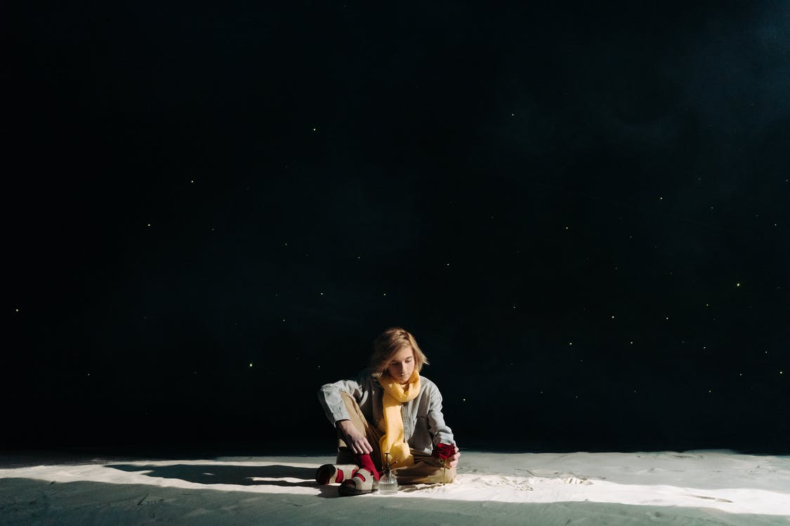 Girl in Pink Jacket Sitting on Sand during Nighttime
