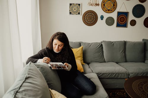 Woman in Black Sweater Painting while Sitting on the Sofa