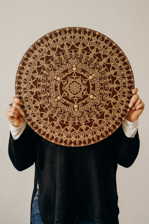 Person Holding Brown and Gold Mandala Decor