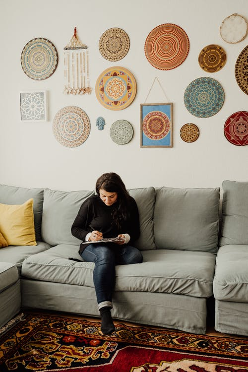 Woman in Black Jacket Painting while Sitting on Sofa