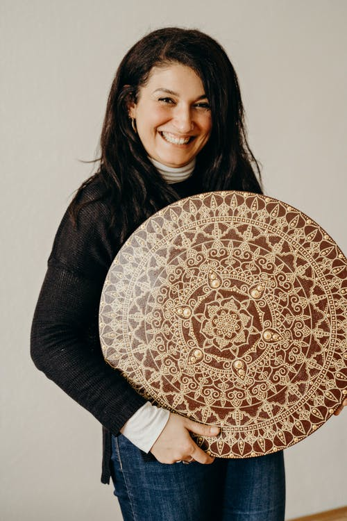 Woman in Black Sweater Holding a Brown and Beige Mandala