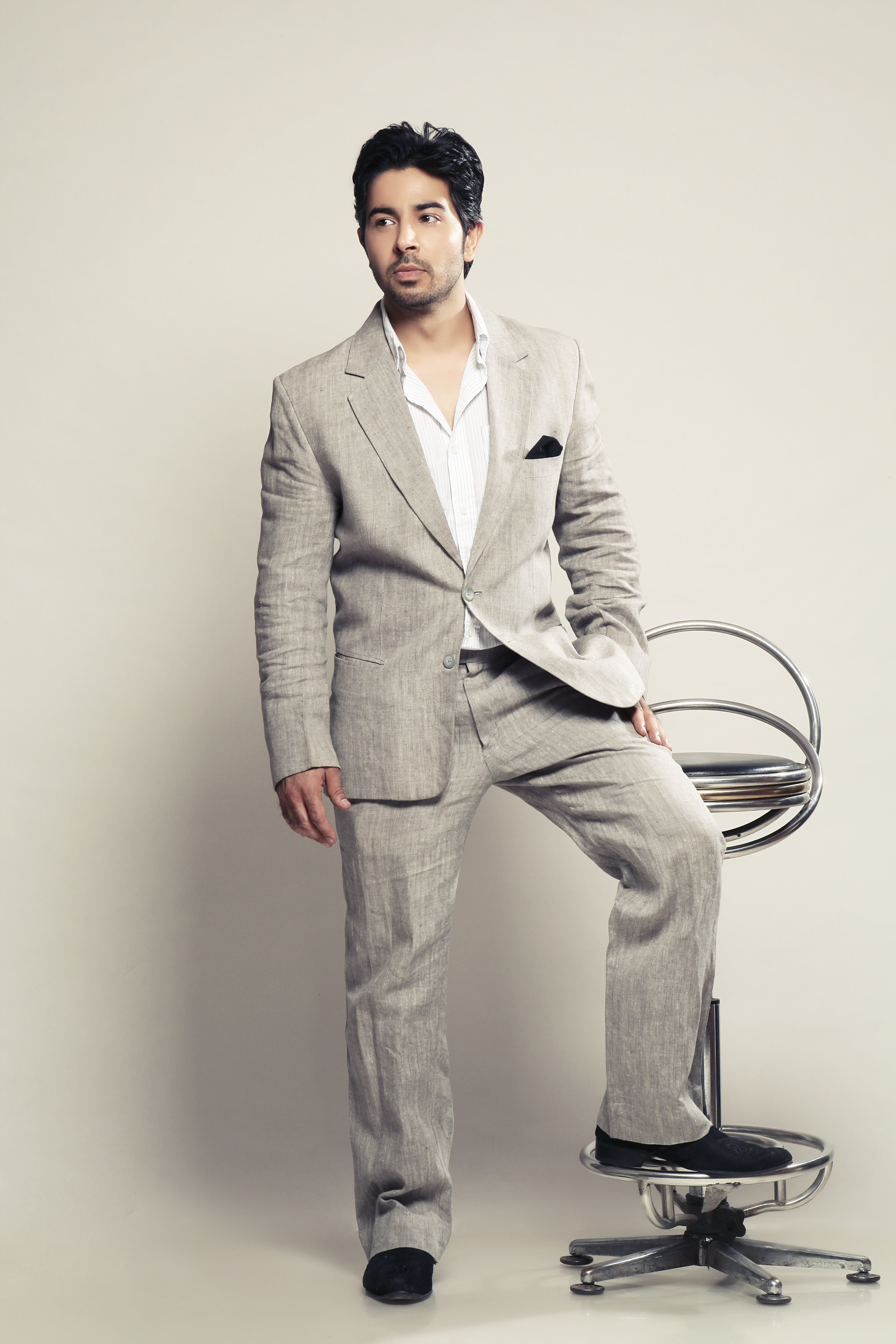 Free stock photo of man in grey suit, man resting his foot on a chair