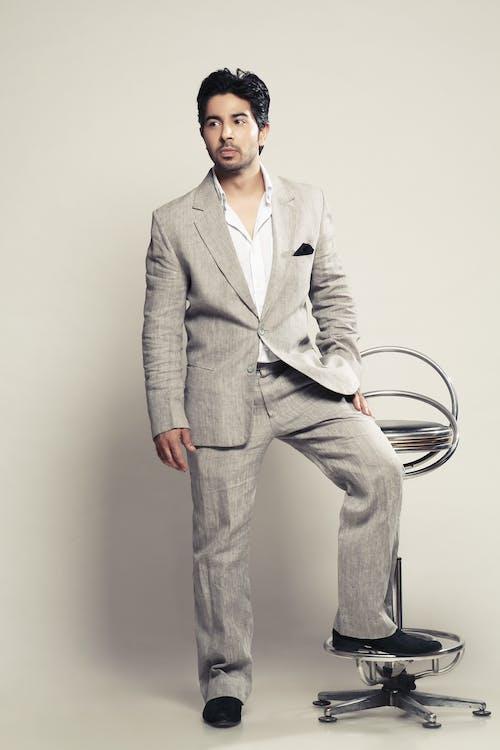 ayağını bir sandalyeye oturan adam, gri takım elbiseli adam içeren Ücretsiz stok fotoğraf