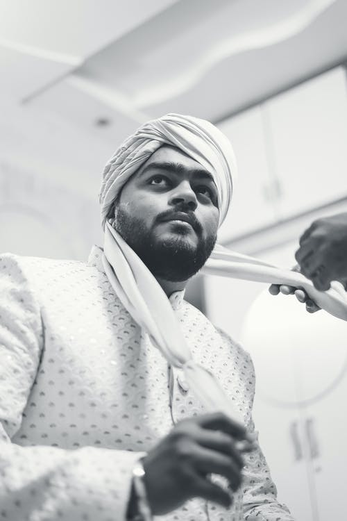 Grayscale Photo of a Man with a Beard Putting on a Turban